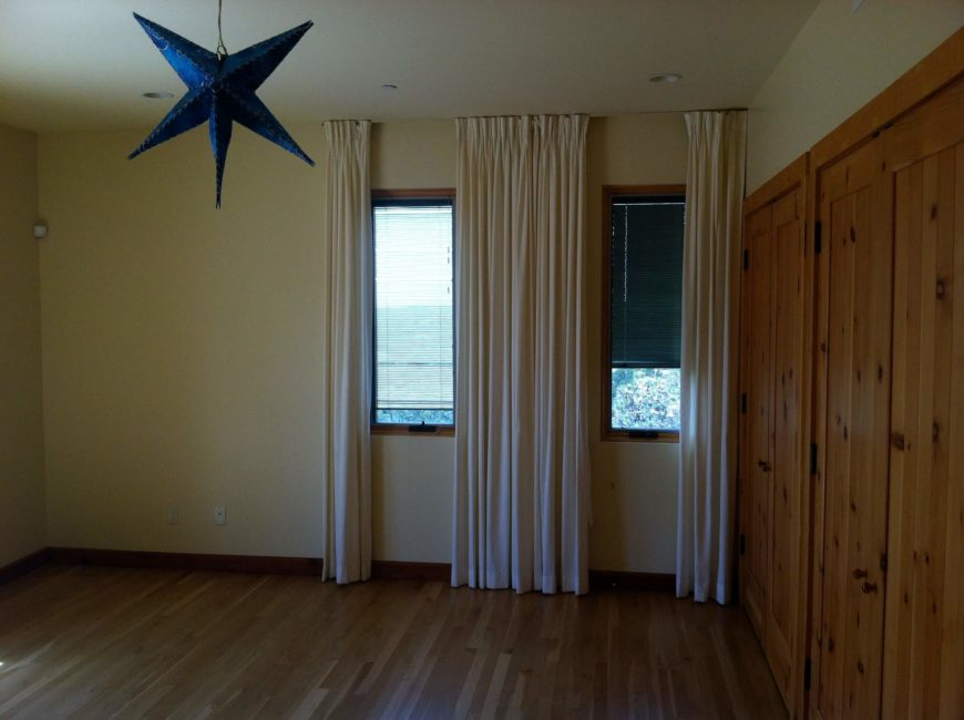 This photo is the before image, a blank canvas for French and French to fill with their ideas. The window on the left is covered up by the tall headboard of the bed, and the curtains were removed in favor of more natural light.