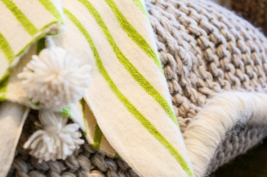 A closeup of the thick weave of the seat and the soft blanket with tassels.
