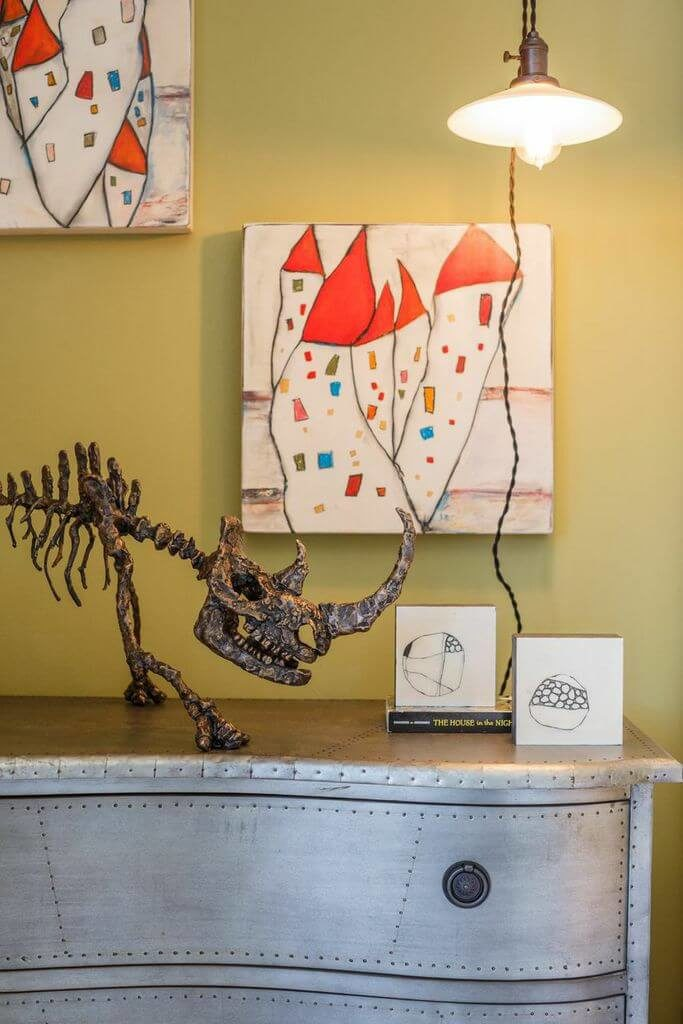 The metallic dresser has a nailhead trim that gives the piece an industrial look. From this view we can see the detail on the bronze rhino sculpture and the paintings behind it.