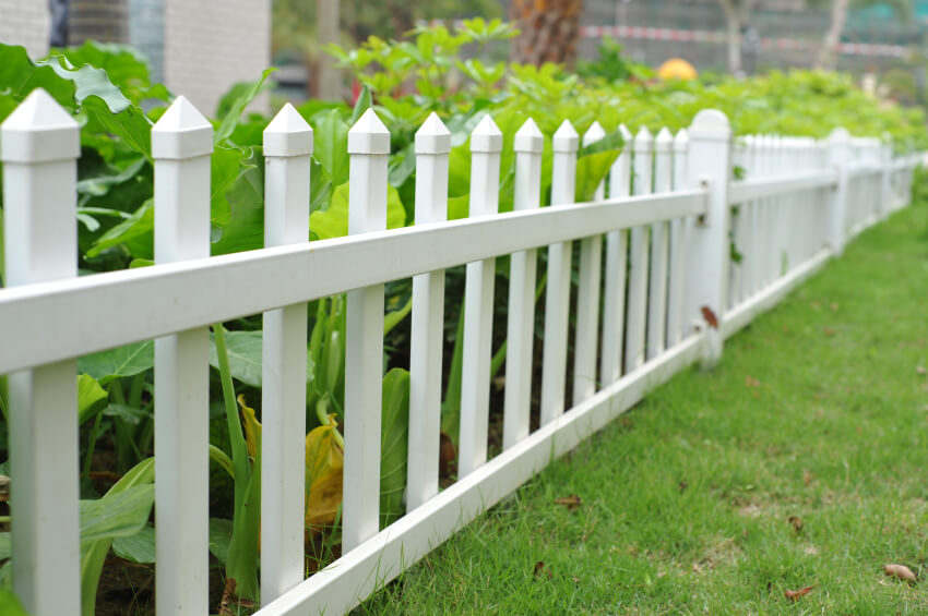 A tiny little aluminum fence to visually separate a garden from the rest of the yard.