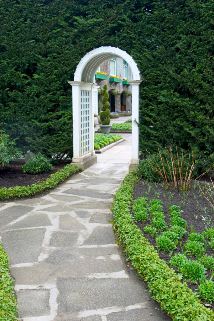 Charmant Fresh Greenery Is A Bright Contrast To The Arched, White Garden Trellis.