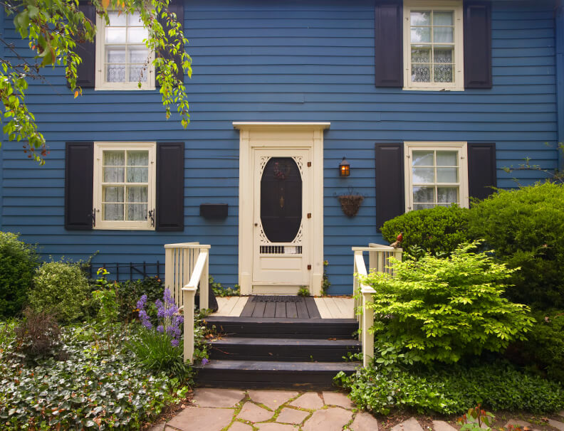 Blue House With Ornate Cream And Dark Blue Door