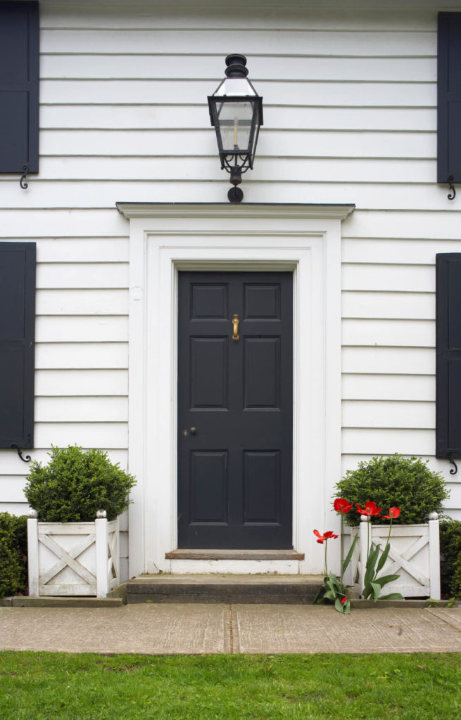 This subtle black door matches the shutter tones creating contrast with this white home painted