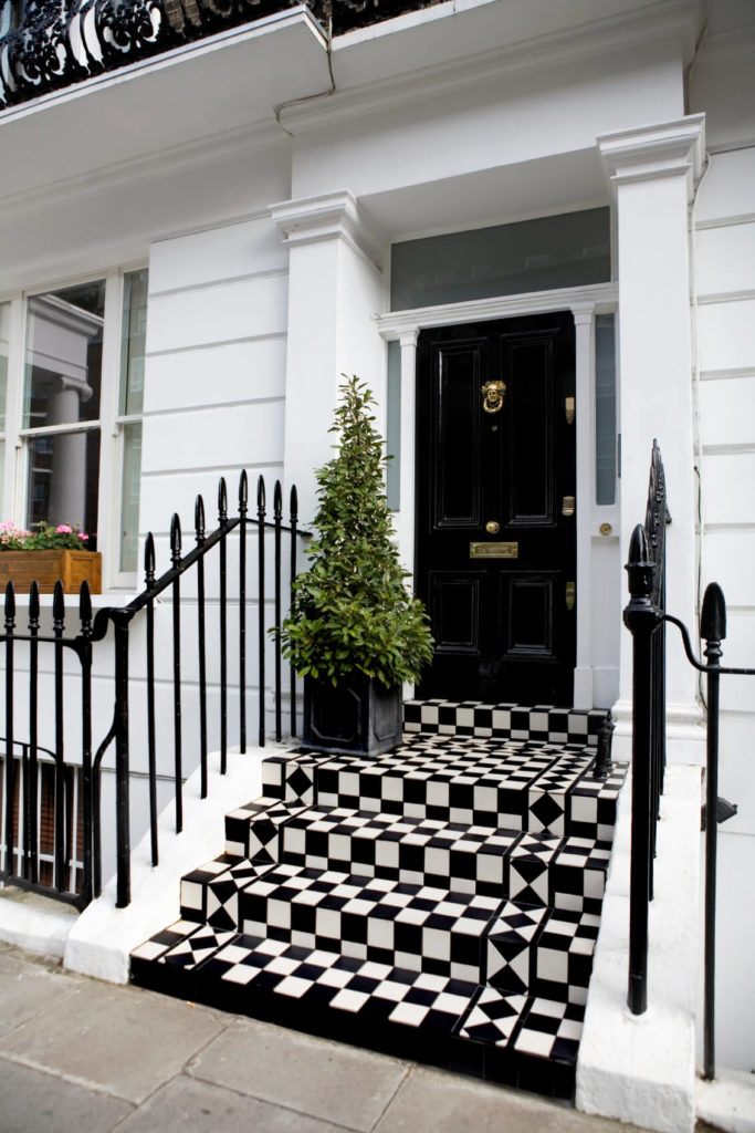 Standing Over A Vibrant Checker Patterned Set Of Steps, This Black Door  Features A Plethora