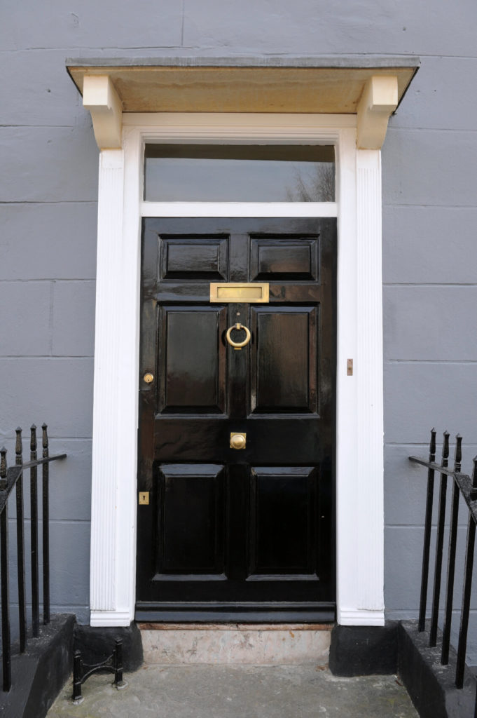Wrought Iron Railing Leads To A Lustrous Door With Circular Knocker And  Brass Mail Slot.