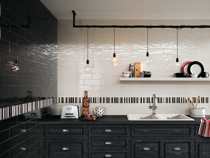 The main work area of this kitchen is tiled in black and white tiles that complement the distressed charcoal cabinets. A stripe of black, white, and gray tiles runs two tiles above the countertops, breaking up the flat colors of the rest of the walls.