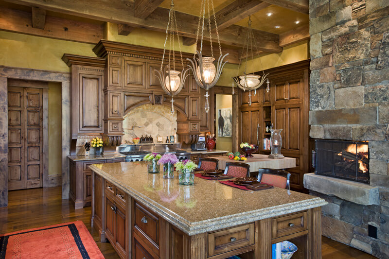 A Grand Rustic Country Kitchen With A Stone Fireplace And Distressed Cabinetry And Trim