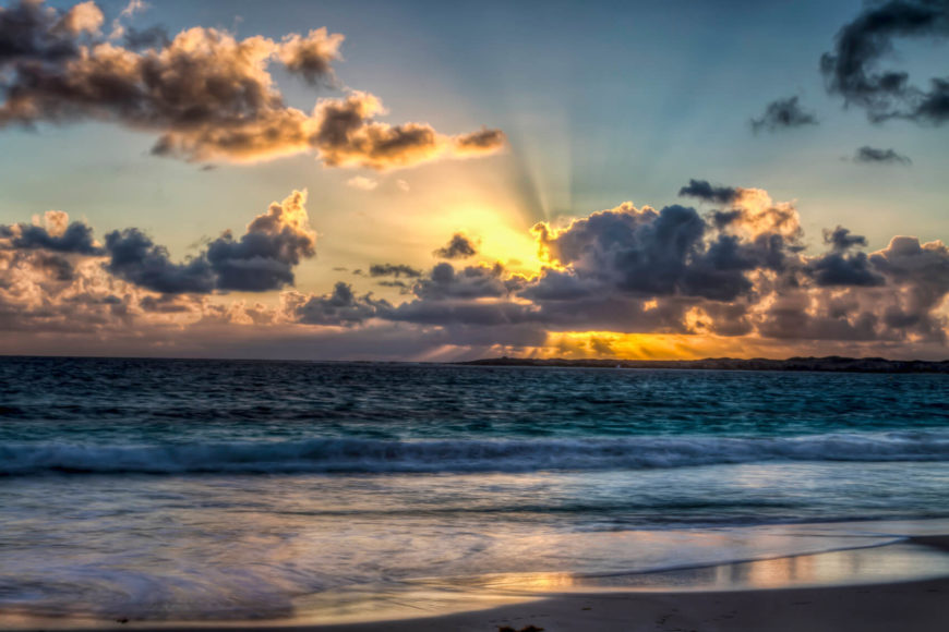 A sunrise view of the gentle waves rolling up onto the white sand shore. This beach is located on the French side of the island on the east coast. The beach has quickly become the most popular beach on Sint Maarten.