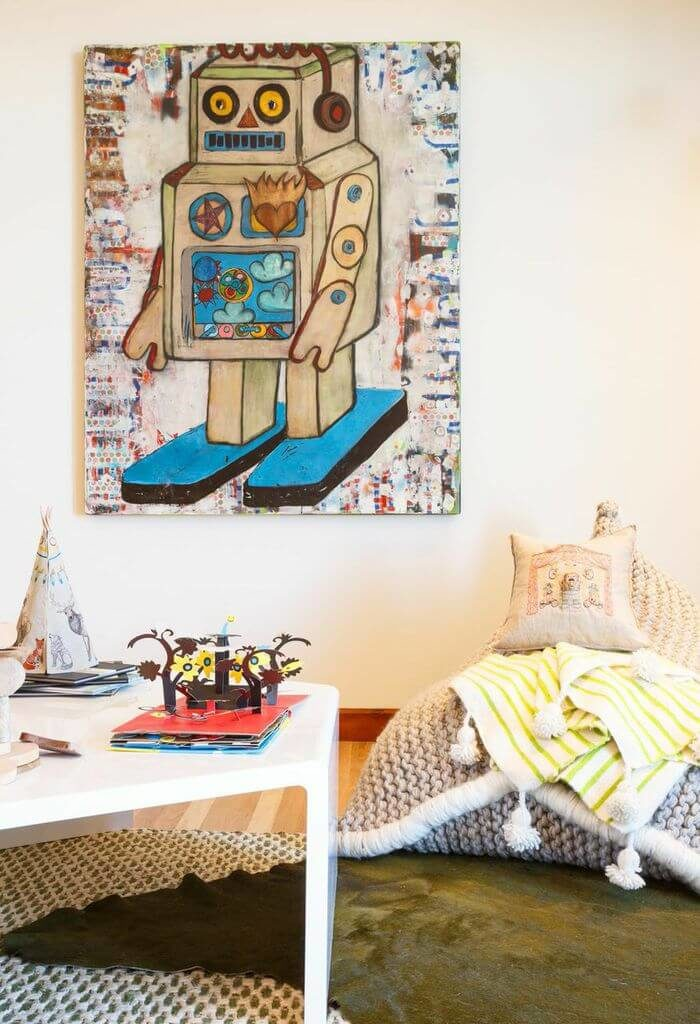 The white modern play table sits near a very soft and highly texturized reading chair. The large weave of the fabric, coupled with a soft, striped blanket, makes for a cuddly corner nook
