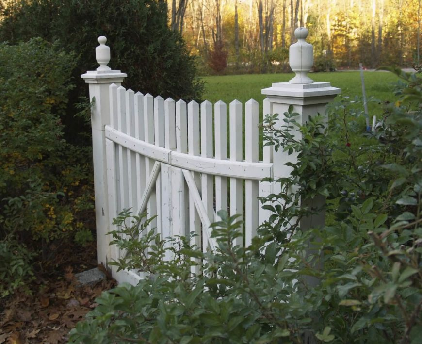 A row of manicured hedges acts as the perimeter fence, with an aged white picket fence gate at the entrance and exit.