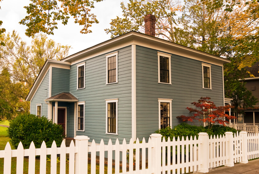 A charming blue home with a low picket fence surrounding the perimeter of the yard. A small gate on one side leads to a walkway to the front door.