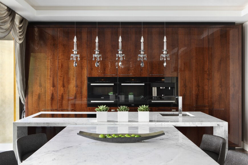 rich glossy hardwood cabinetry and t shaped marble island the island