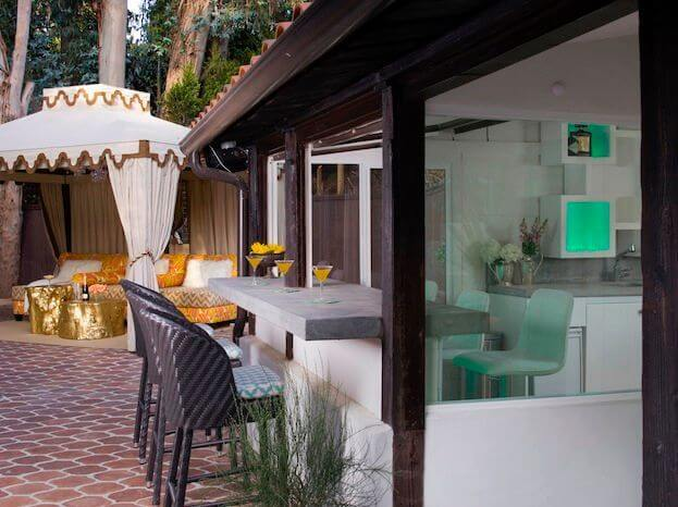 As the backyard wraps around, the pool house comes into view, with a cabana nearby. An eat-in bar with a passthrough connects to the modern interior, creating from this angle a shift in styles.