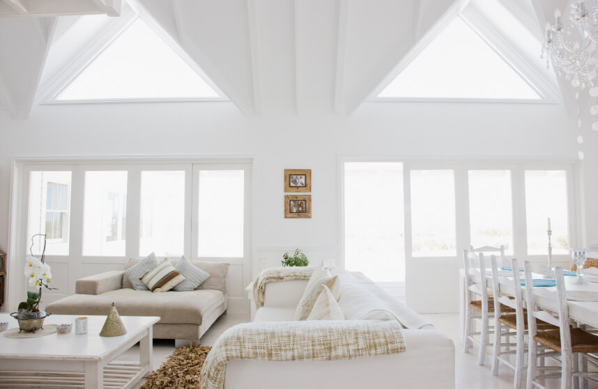 Two Grand Skylights Stand Out In This High Ceiling Living Room. The All  White