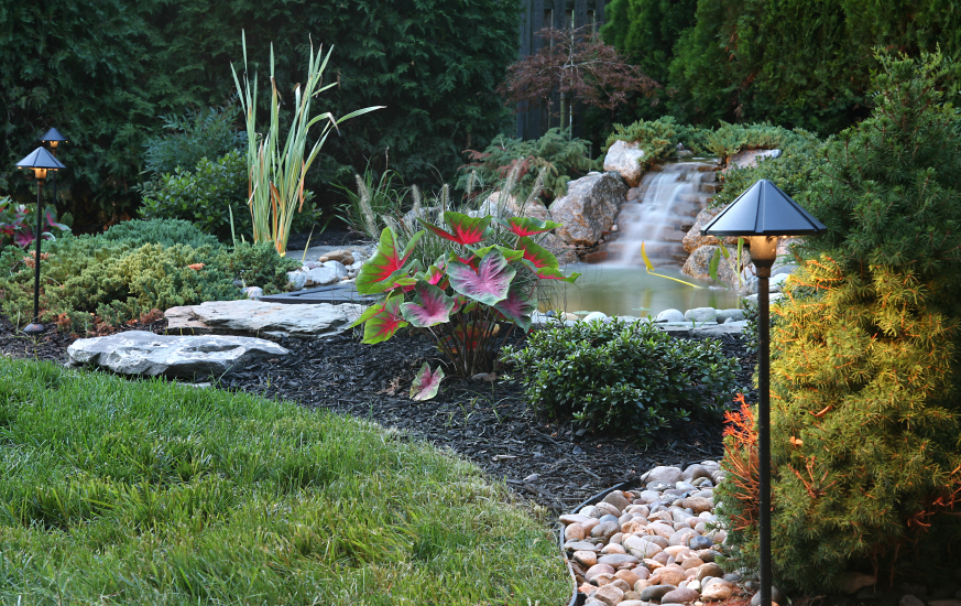this pond with a stone waterfall is slightly off the beaten path of the yard - Waterfall Landscape Design Ideas