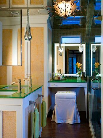 The pool house bathroom is spacious and modern with whimsical lighting and dual sinks. It also includes a makeup vanity.