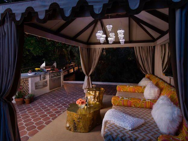 The cabana by the pool house is filled with luxurious, deep seating perfect for lounging. Stump tables painted gold act as coffee tables. An outdoor cooking range and grill are visible just to the right of the the cabana.