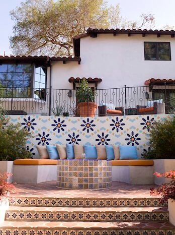 On a lower tier, mosaic tiles and patterns surround a built-in bench.