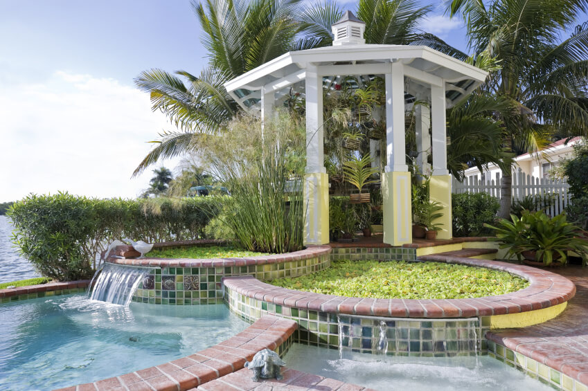 A series of pools leading down from a glass-topped gazebo. The top two pools are filed with green water plants, with small fountains that cascade into one small pool and the larger swimming pool.