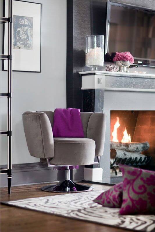 A close up on the living room's wood burning fireplace and the modern beige suede chair next to it. A fringed cashmere throw blanket in a beautiful bold berry purple is slung over the back of the rounded chair. The beautiful black soapstone around the fireplace adds an air of elegance.