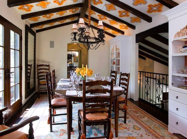 The formal dining room has large china cabinets on either side of the small wrought iron balcony that overlooks the living room. This space is very contemporary, but the yellow stencils on the ceiling between the exposed wooden beams add unique charm.