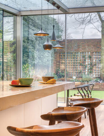 A close up on the fantastic, beautiful wooden barstools, polished to a sheen and adding a natural flair to the very modern, contemporary kitchen.