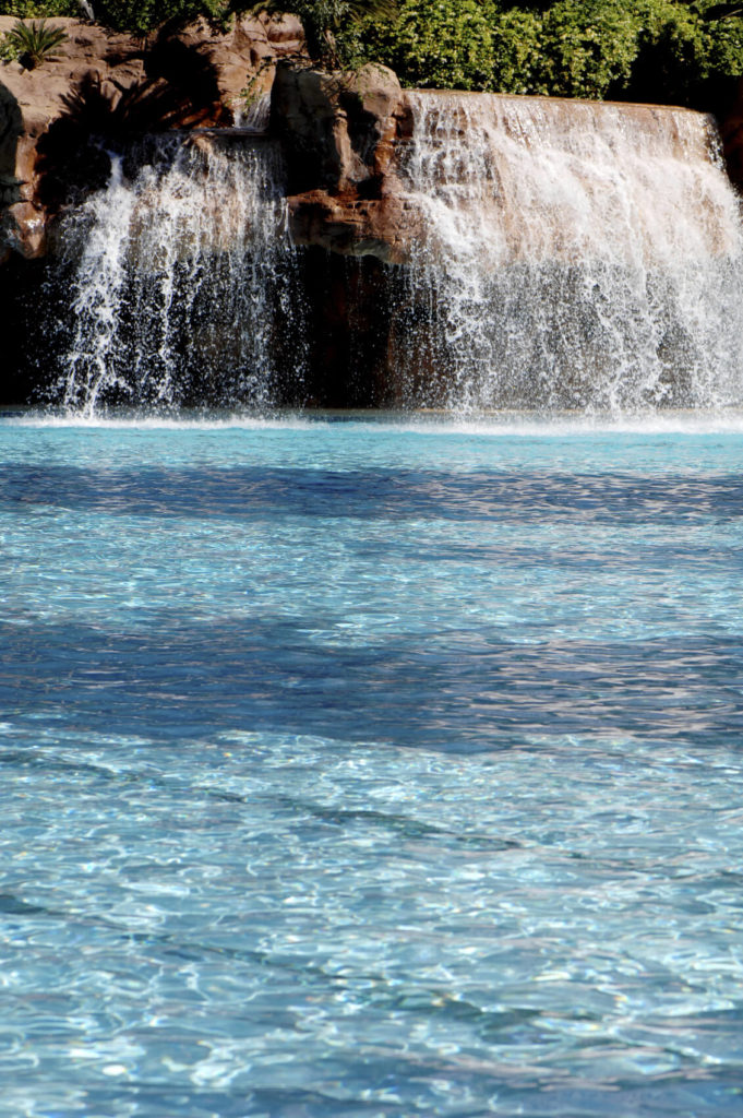 An artificial waterfall tumbling down into a pool. The flow of the water and the artificial stones are engineered to match the flow and look of a natural waterfall as much as possible.