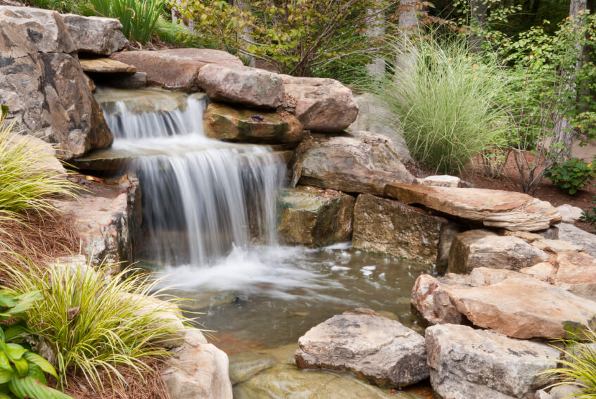 the easiest way to make a garden waterfall look and feel natural is to surround the - Waterfall Landscape Design Ideas