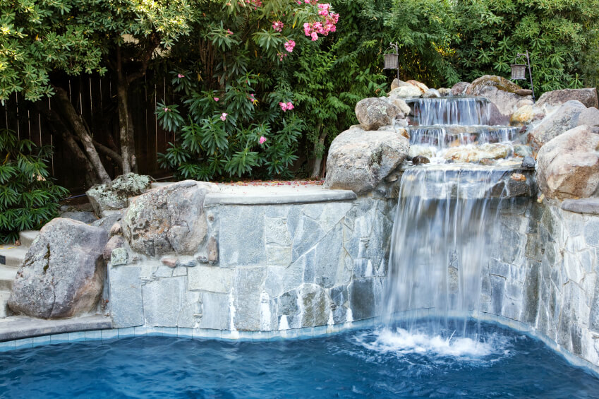 A set of concrete steps follows the curve of the pool and are hidden by the stone wall and stacked natural stones that create a three-tier waterfall.
