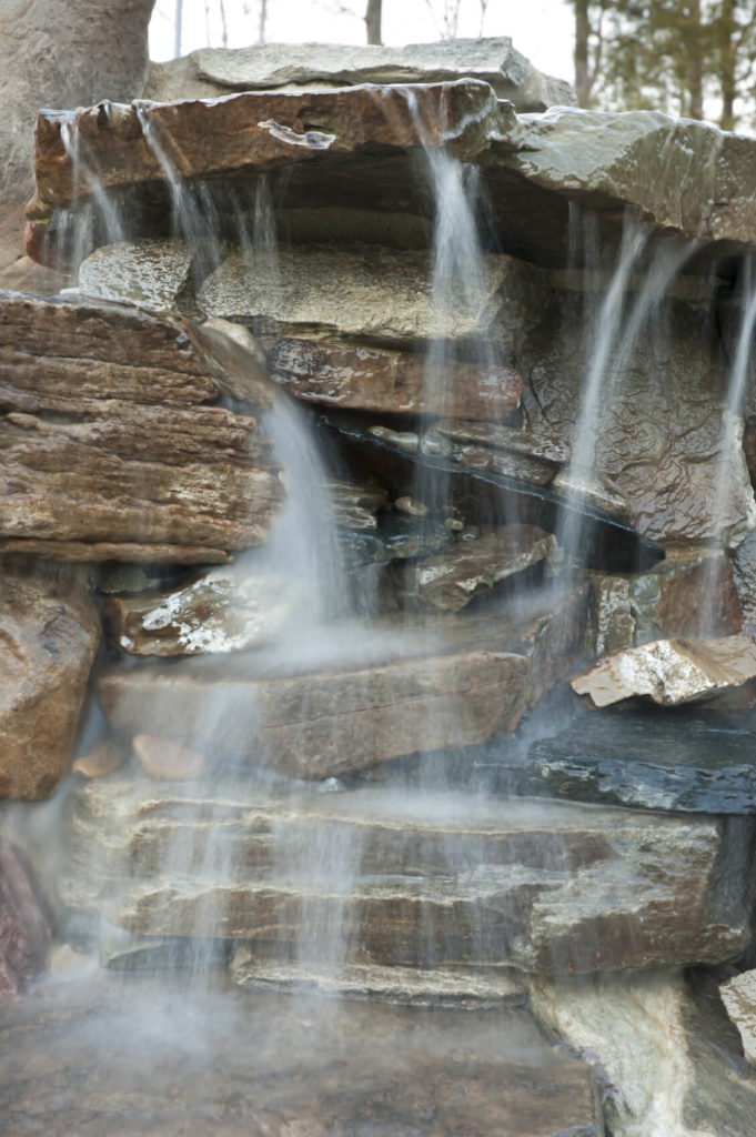 A Close Up Of A Waterfall Where The Water Hits Multiple Rock Surfaces On  The Way