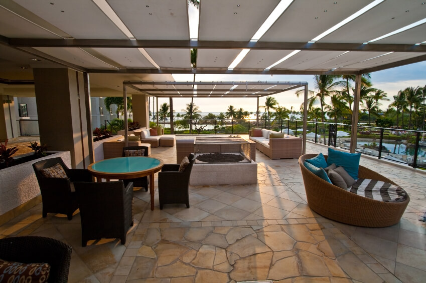 this stone tile patio features a number of different seating options including a circular lounge - Different Patio Designs