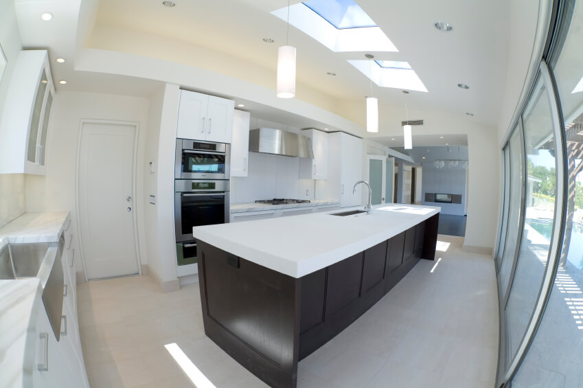 Superior Rich Dark Hardwood Contrasts The Polished Whites And Marble Of This Kitchen.  The Skylights Dapple