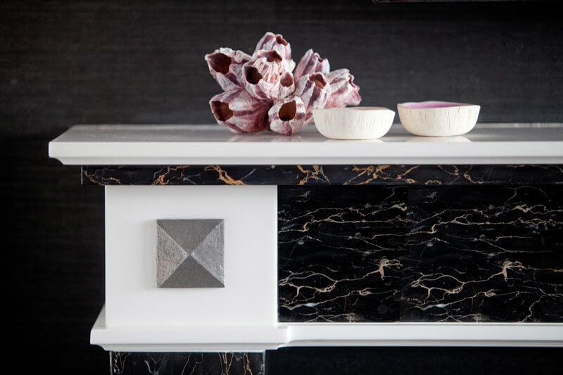 A close up on the mantle, showing the veining in the beautiful stone and the details. The simple coral decorations pull in the bold berry color in a softer, more natural hue.