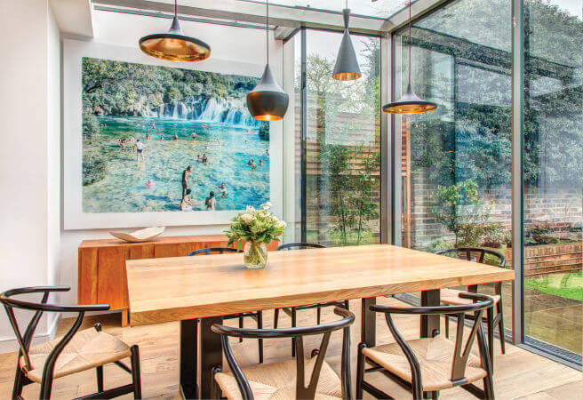The glass extension contains the sleek dining room set in dark and light wood with natural fiber seats. A large painting of a waterfall scene hangs on the back wall above a natural wood table in yet another shade.