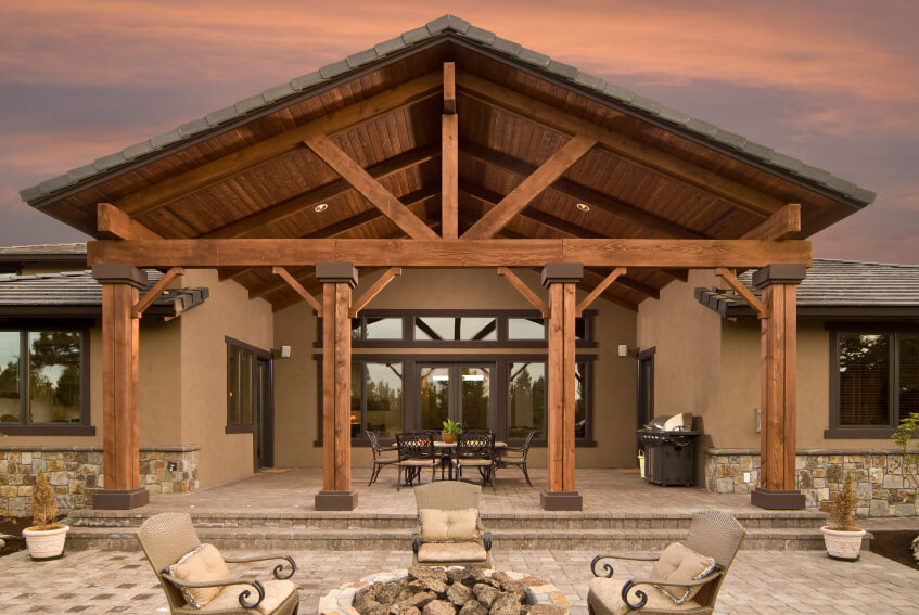 even the rear of this home includes a grand architectural statement tall wooden beams lead - Patio Cover Ideas Designs