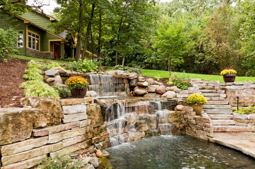 A house on a hillside features a rolling waterfall beside the stone steps that lead down to a spacious patio area.