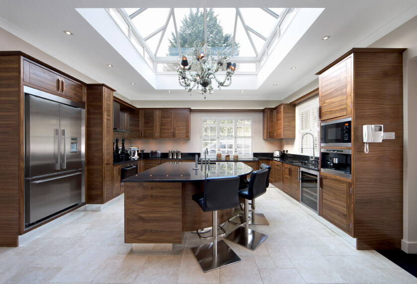 This kitchen is elegant and full of dramatic wood work. A massive skylight  takes up