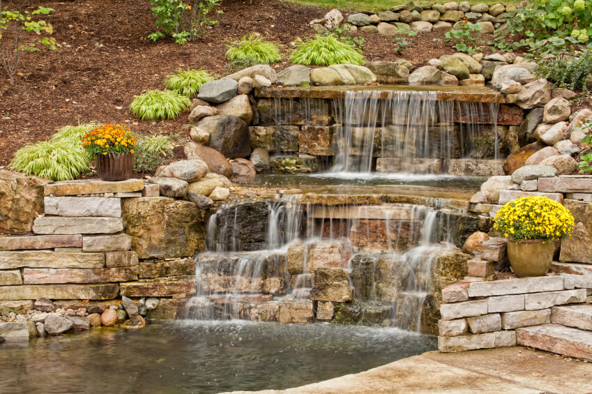 a final look at the waterfall showing the way the water rolls down multiple rock - Waterfall Landscape Design Ideas