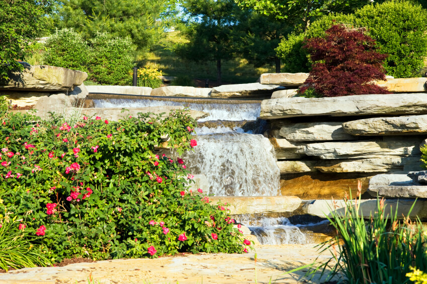 this garden waterfall has a small ledge of rock extending like a miniature bridge over one - Garden Waterfalls