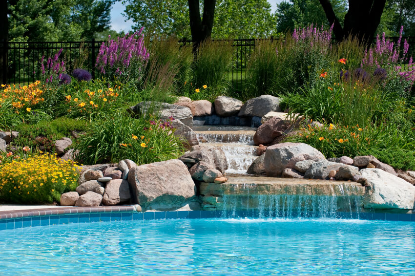 a beautifully created stone waterfall with a reservoir surrounded by daylilies and other beautiful flowering bushes - Swimming Pools With Waterfalls
