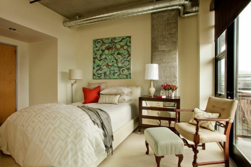 One of the condo's two bedrooms has a door to a balcony and exposed venting. The long bed has a rolled, upholstered headboard that adds an air of sophistication to the concrete support beam behind the mirrored-front nightstand.