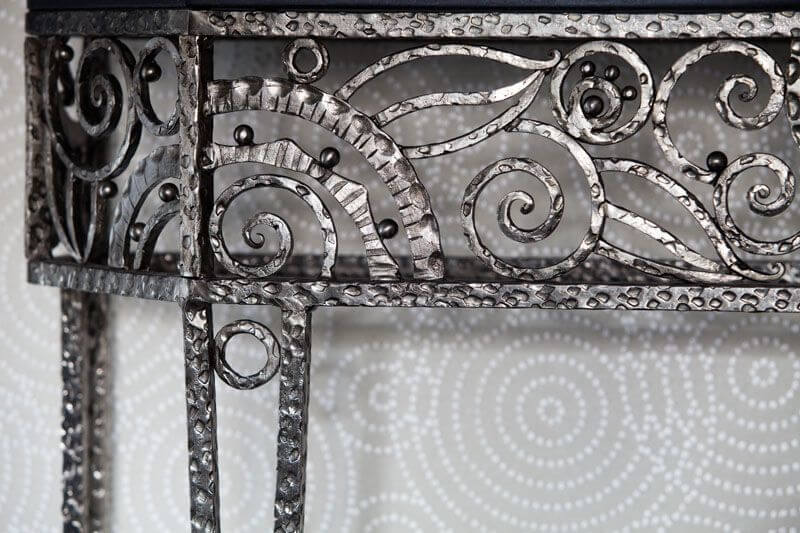 The small entryway into the apartment has an ornate wrought iron side table against a light gray wallpaper with white concentric circles.