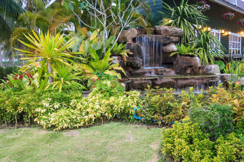 A Stone Garden Waterfall Near The Side Of The Home Surrounded By Large  Tropical Plants.