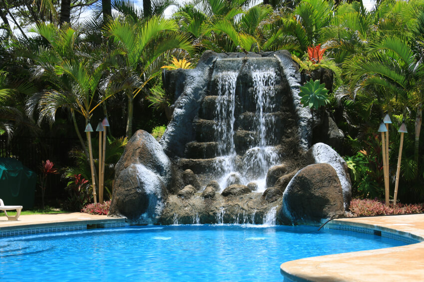 An enormous multi-tiered artificial waterfall flowing into the far edge of a standard in-ground pool. Tropical landscaping and tiki torches set the theme of this backyard lagoon.