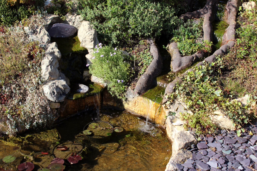 """From above, the artificial """"bumpers"""" of the multiple streams are clearly visible. Two empty into the larger waterfall, while the other enters just off to the left. The reservoir at the bottom is clear, with many lilypads."""
