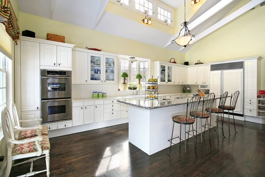 This bright yellow kitchen sits below an immense vaulted ceiling with upper  level windows carved into