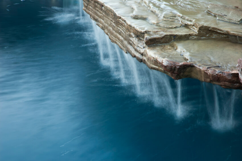 Water pouring off the edges of a slate waterfall into a pool.