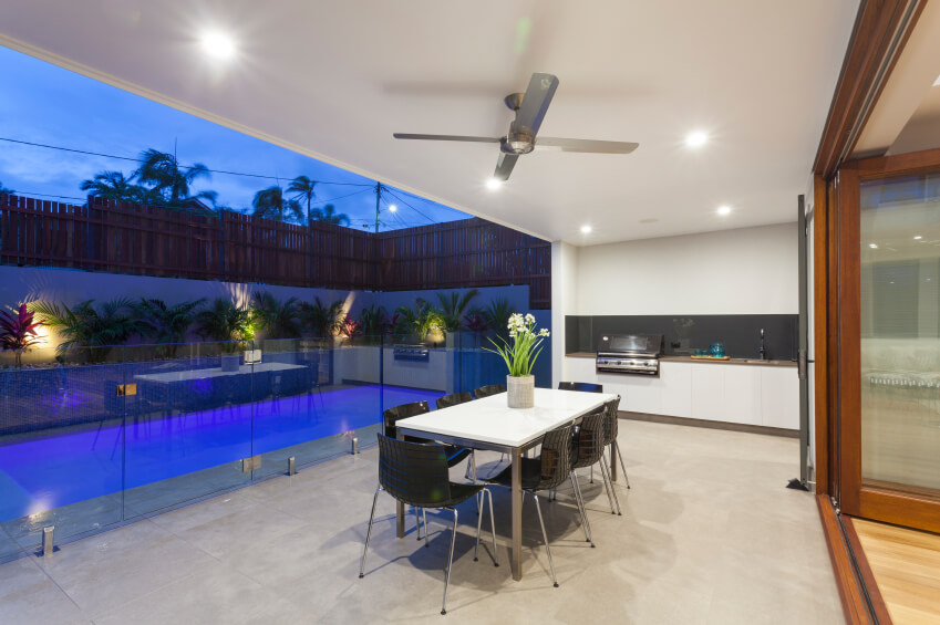 A Glass Balustrade Separates This Covered Stone Patio And Outdoor Kitchen  From The Rest Of The