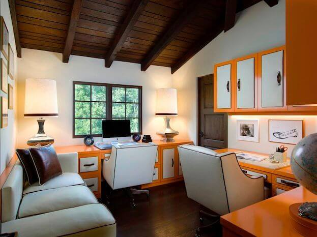 Some modern elements creep into the main home in this double office. Custom orange cabinetry and desk surfaces add an amazingly bright pop of color to the otherwise cream furniture. The desk areas are split into two workspaces: one with a computer, and the other more of a craft area.
