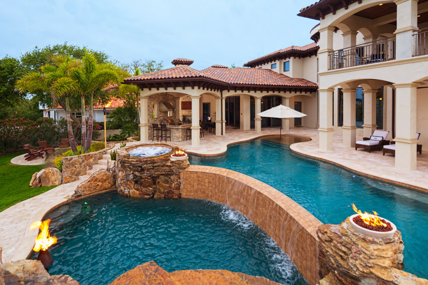A luxurious asymmetrical pool along tall columns and steps that move past the two-tiered pool and into the backyard. The complex also includes a jacuzzi on the left of the top tier.